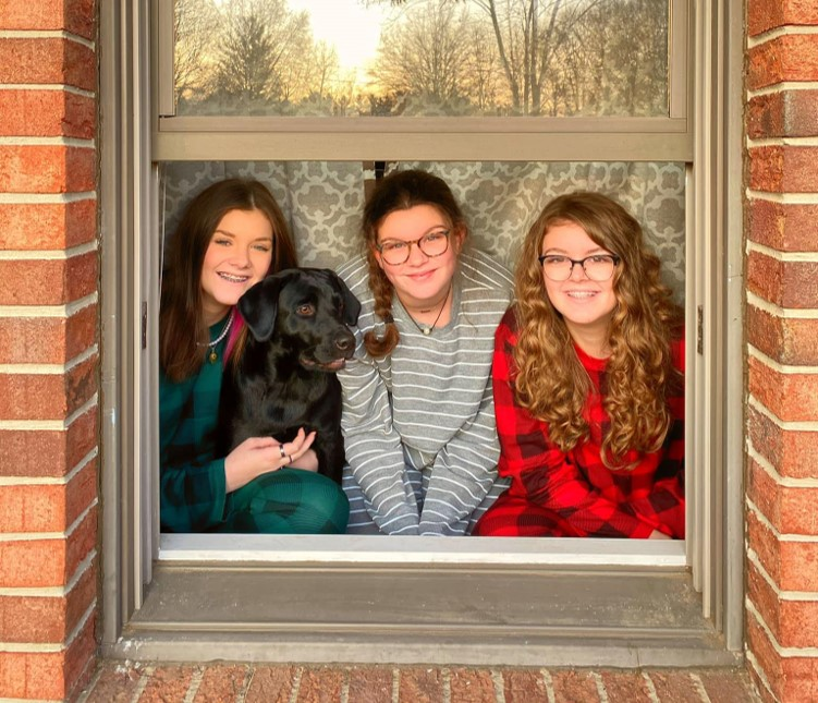 Three girls looking out the window with their dog