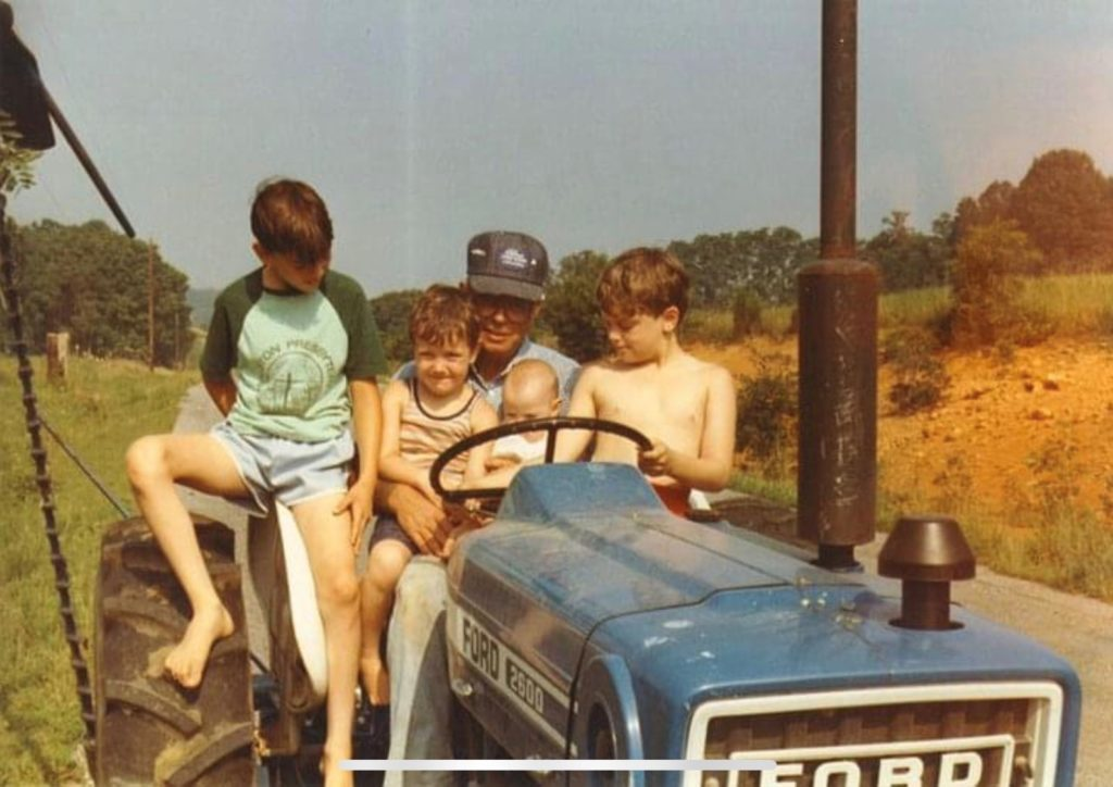four children with a man on a tractor