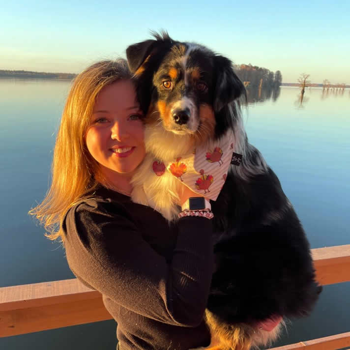 Mary with her dog standing on a dock in front of a body of water