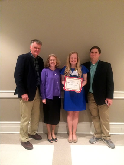Sarah with three other people holding a certificate