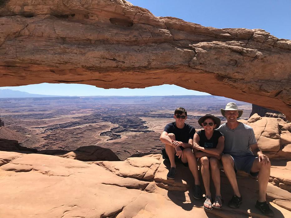 Brynn, her husband and son sitting under a rock arch