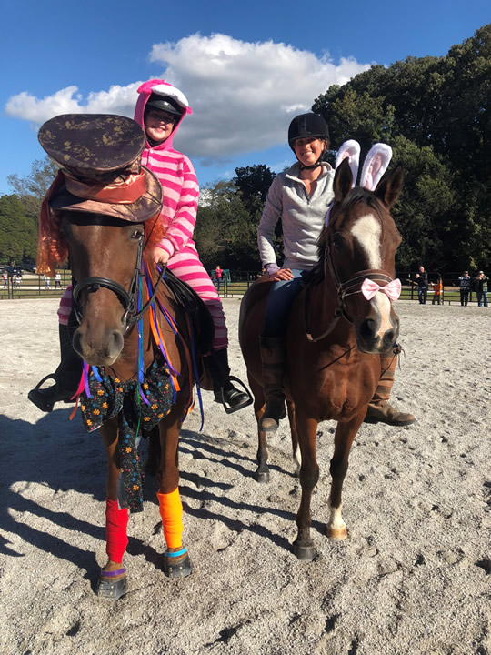 kelly and a friend riding horses that are dressed for halloween