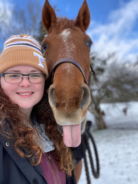 Kelly with a horse that has it's tongue sticking out