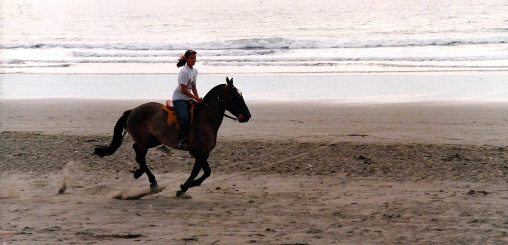 Sonia riding a horse by the ocean