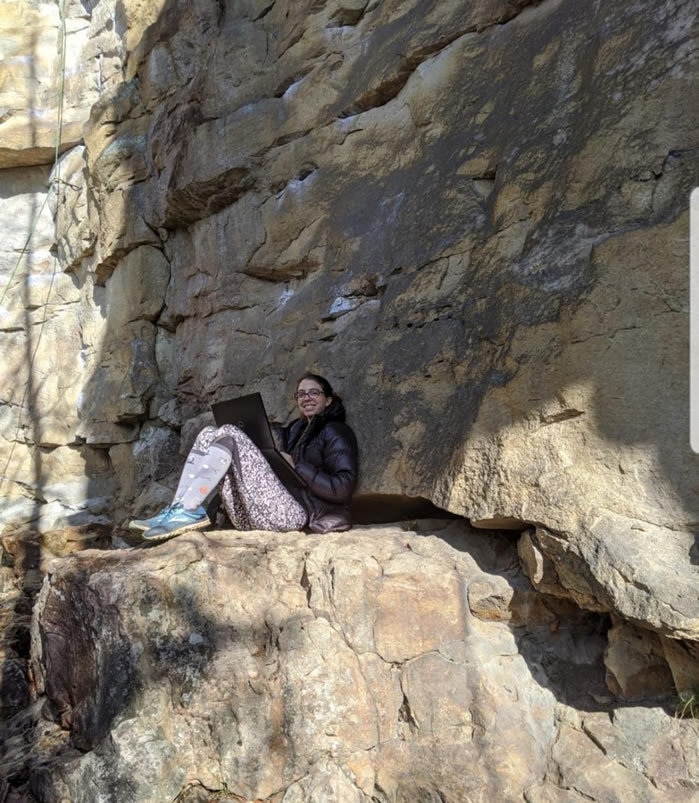 Casey sitting on a rock edge working on her computer