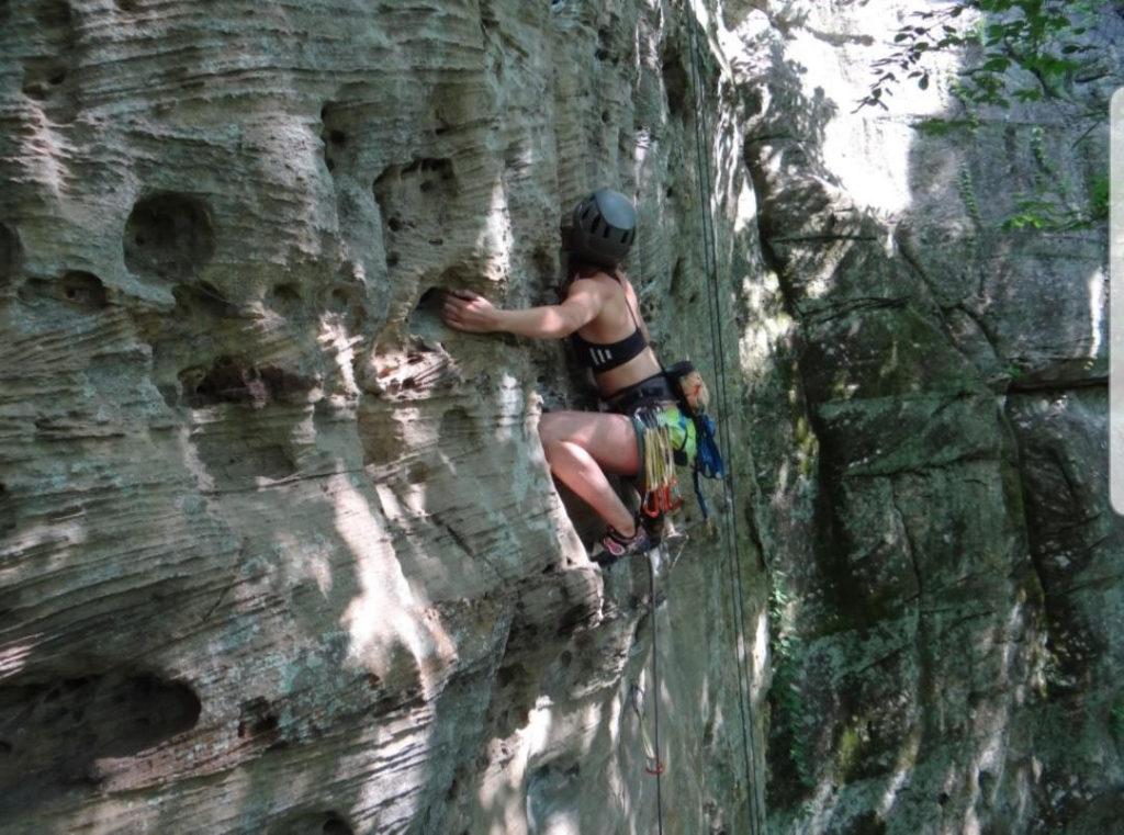 Casey climbing a cliff