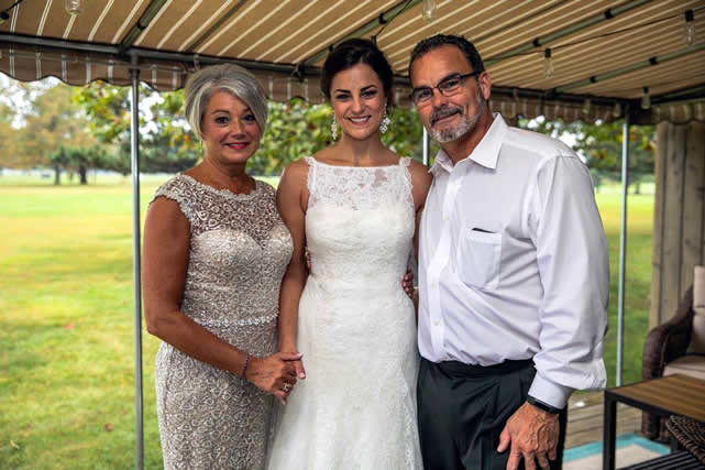 Amanda with her parents on her wedding day