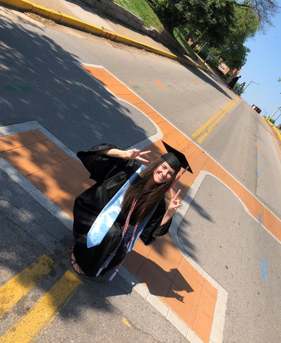 August in cap and gown in front of the BIG T