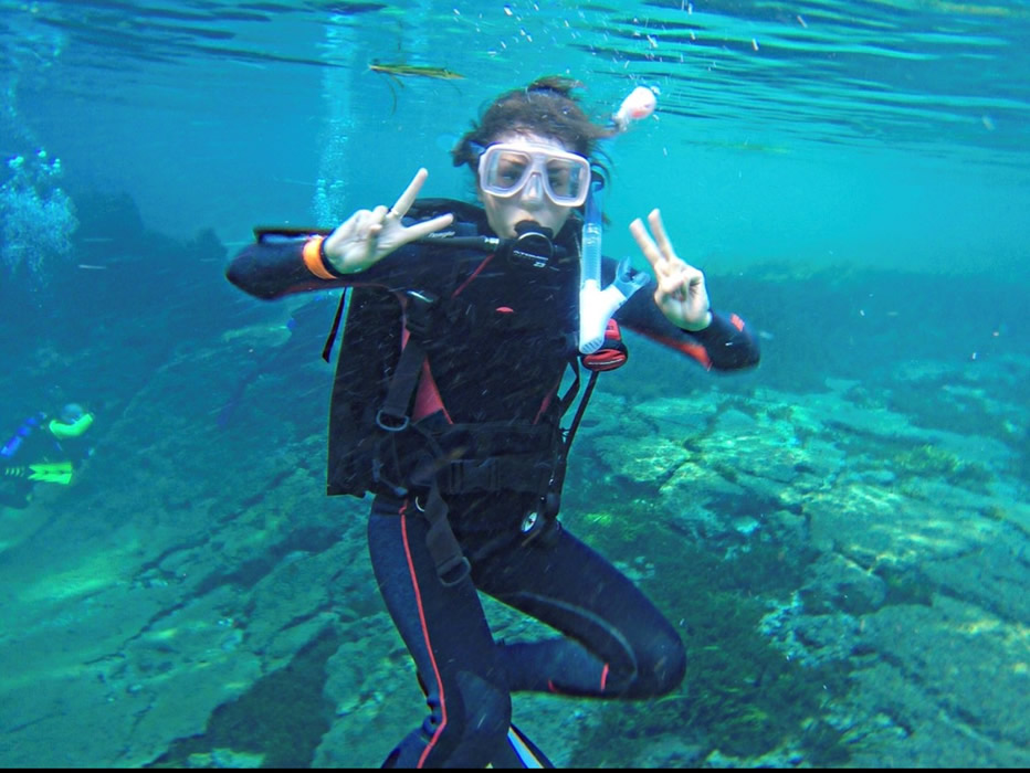 August flashing the peace sign under water