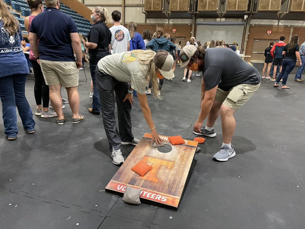Students picking up the bean bags from the cornhole box
