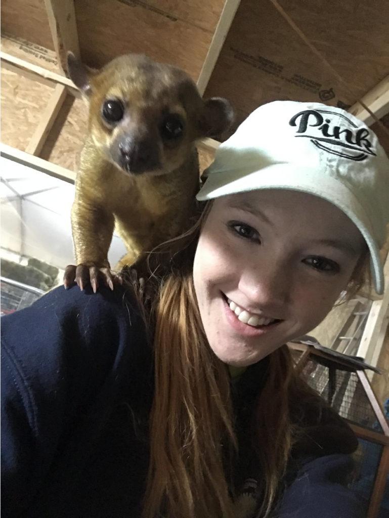 Caitlin with a Kinkajou on her shoulder