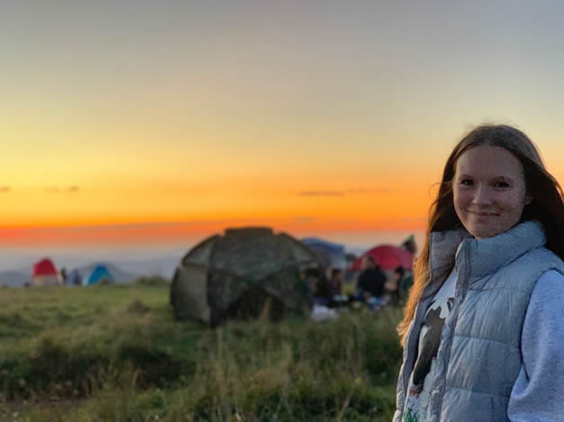 Emma with a sunset behind her