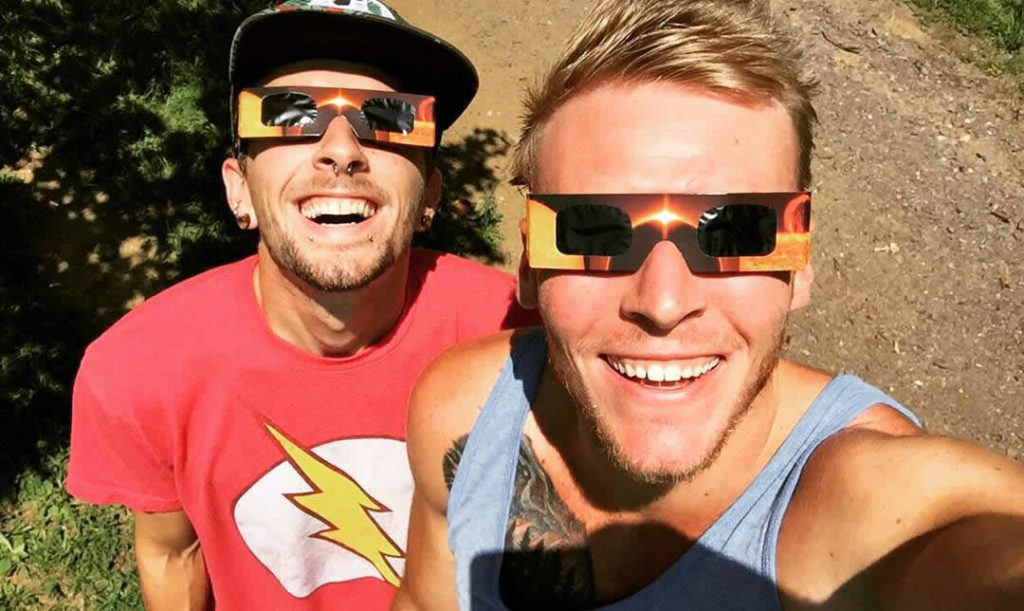Jeremy and a friend posing for a selfie with paper glasses